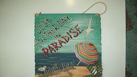 "Image of a ""Just Another Day in Paradise"" Beach Sign"