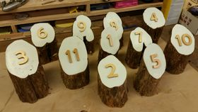 Image of a Rustic-themed table numbers made from red cedar posts.
