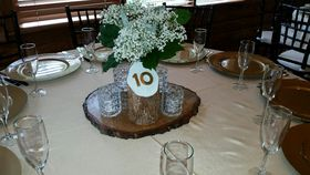 Rustic-themed table numbers made from red cedar posts. image