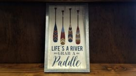 "Image of a ""Life's A River Grab A Paddle"" Sign"