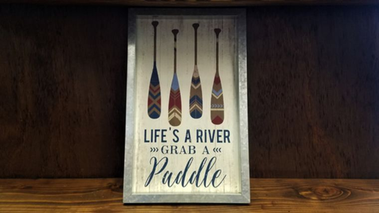 "Picture of a ""Life's A River Grab A Paddle"" Sign"