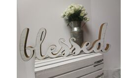 "Image of a ""Blessed"" white distressed wooden table decor"