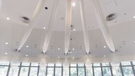 Image of a We will provide and install (5) swags of white fabric to the ceiling of the Auditorium as shown in the attached photo. This fabric will drape down along the windows.