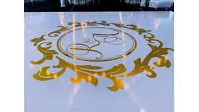Image of a 16 FT x 32FT Gloss White Vinyl Floor Wrap w/ Gold Foil Monogram Design in Center