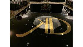 Image of a 16 FT x 32FT All Black Floor Wrap w/ Gold Foil Monogram Design in Center